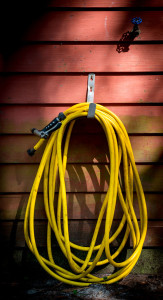 Yellow hose carefully hung below blue spigot.