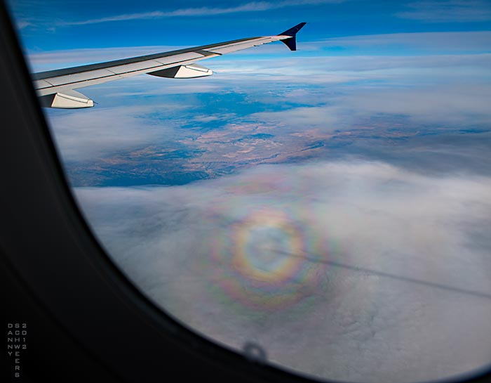 """Photo of concentric rainbows — a """"glory"""" — centered on an airliner's shadow, the shadow of its contrail a straight line to the right. Photo copyright 2012 and text copyright 2021 by Danny N. Schweers."""