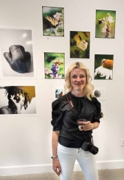Photographer Kathleen Magner Rios with her photos above her.