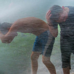 Young men in stinging water spray